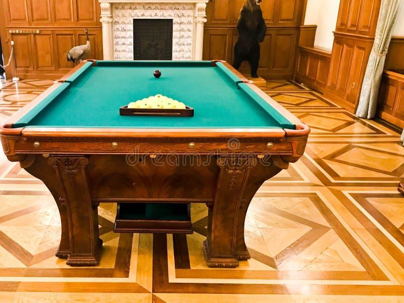 Grote houten massieve dure poollijst met een groene doek voor het spelen van biljart stock afbeeldingen