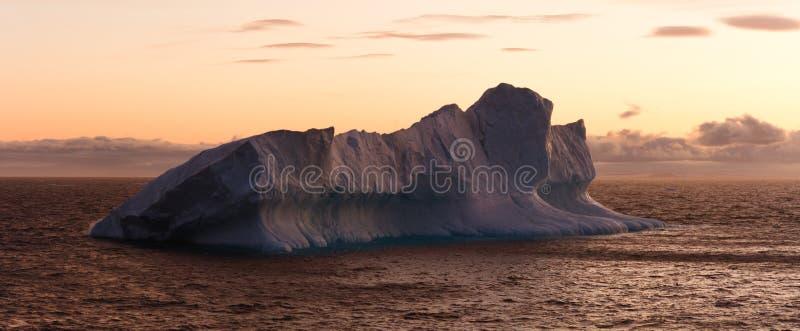 Grote Ijsberg die in Overzees bij Schemer drijft royalty-vrije stock fotografie