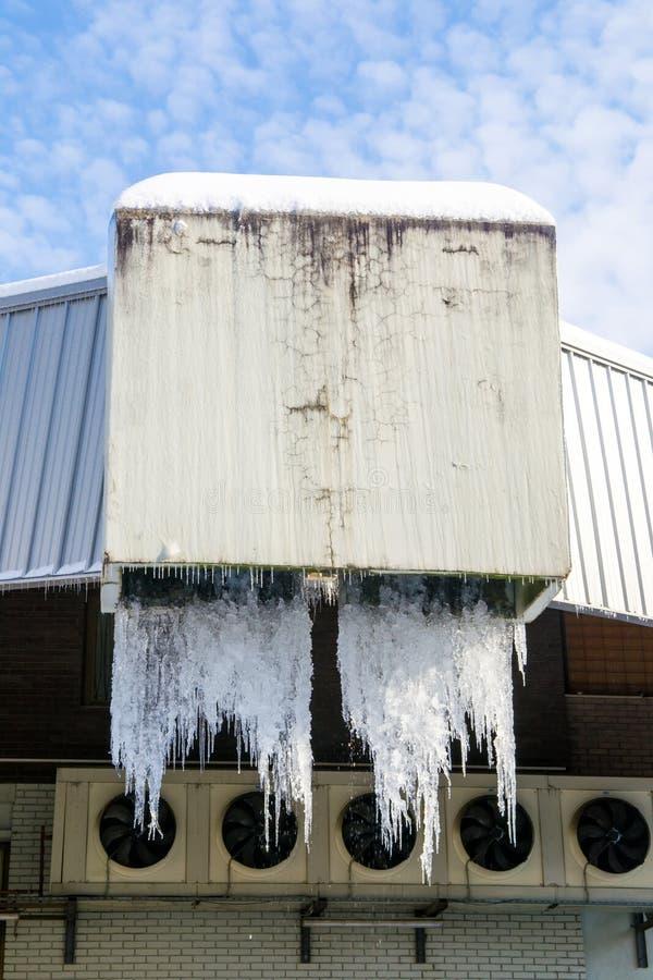 Grote ijskegels die van industriële afvoerkanalen hangen royalty-vrije stock afbeelding
