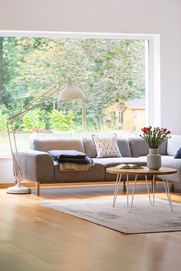 Grote, industriële stijlstaande lamp boven een elegante bank in een wit en natuurlijk, Skandinavisch woonkamerbinnenland met een  stock foto's