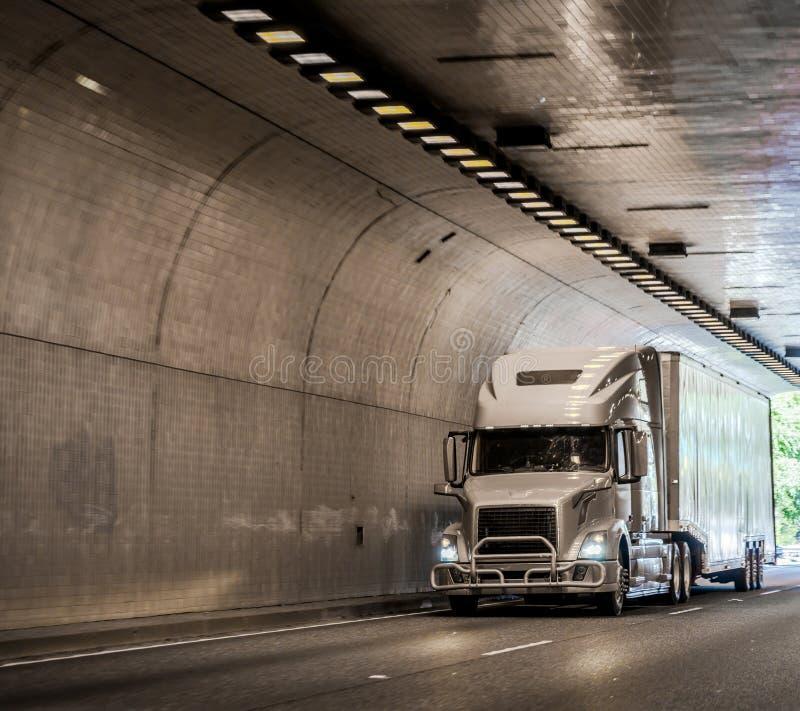Grote installatie grijze semi vrachtwagen die lading in droge bestelwagen semi aanhangwagen vervoeren die in overspannen die tunn stock afbeeldingen