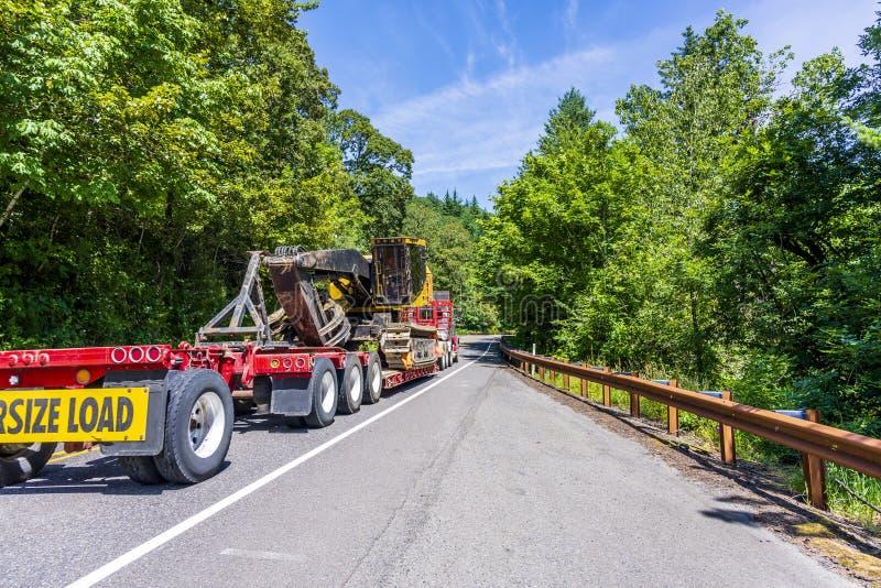 Grote installatie krachtige semi vrachtwagen die overmaats graafwerktuig op stap - onderaan semi aanhangwagen met het overmaatse  stock foto