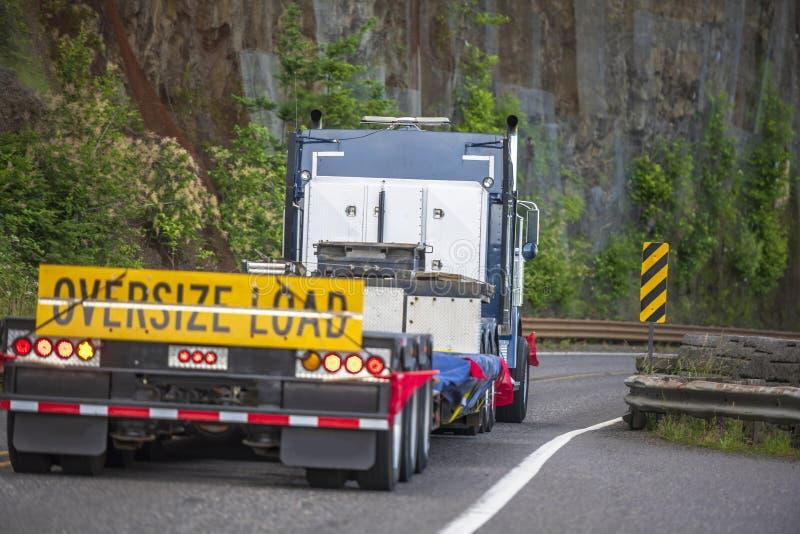 Grote installatie semi vrachtwagen met teken overmaatse lading achter het vlakke bed semi aanhangwagen drijven op de bergweg met  royalty-vrije stock foto's
