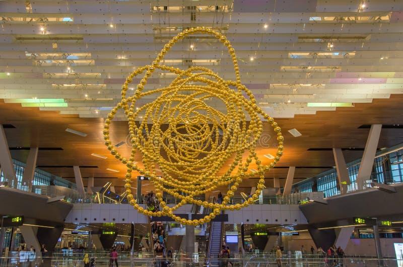 Grote installatie van gouden parelparels in plafond in luchthaven Hamad van Doha, Qatar stock foto