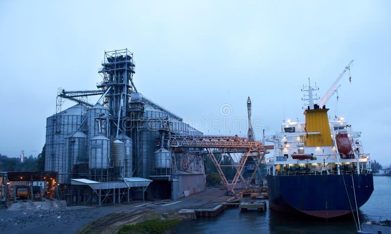 Grote korrelterminal bij zeehaven Graangewassen bulkoverscheping van wegvervoer aan schip De gewassen van de ladingskorrel op sch stock fotografie