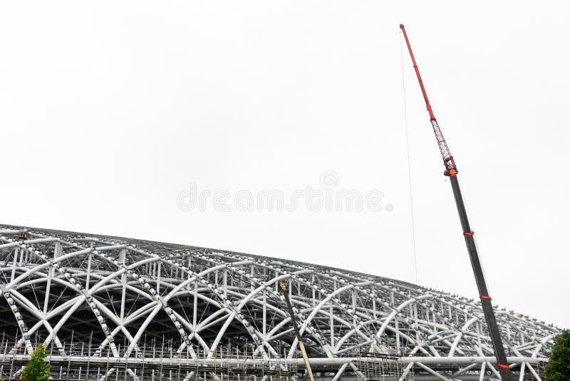 Grote kraan op het metaalkader van stadiondak, de bouw van nieuwe sportarena, die op witte achtergrond wordt geïsoleerd stock foto