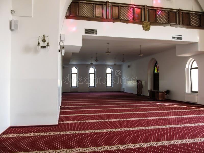 Grote lege zaal met rood tapijt, lijst en witte muren van de Moskee AR-Rahma in Kiev stock afbeeldingen
