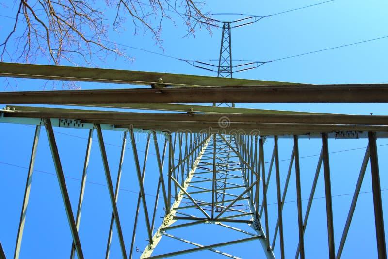 Grote machtspyloon die elektriciteit op een plattelandsgebied vervoeren stock foto