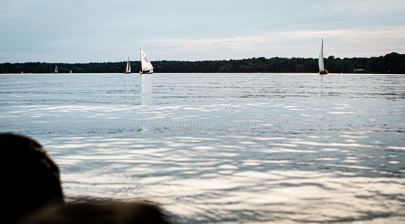 Grote mening over een kalm meer met varende boten stock foto