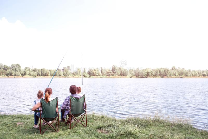 Grote mening van het grote rivier stromen Er zijn een familiezitting door zijn kust en het genieten van het van ogenblik Zij houd royalty-vrije stock foto's