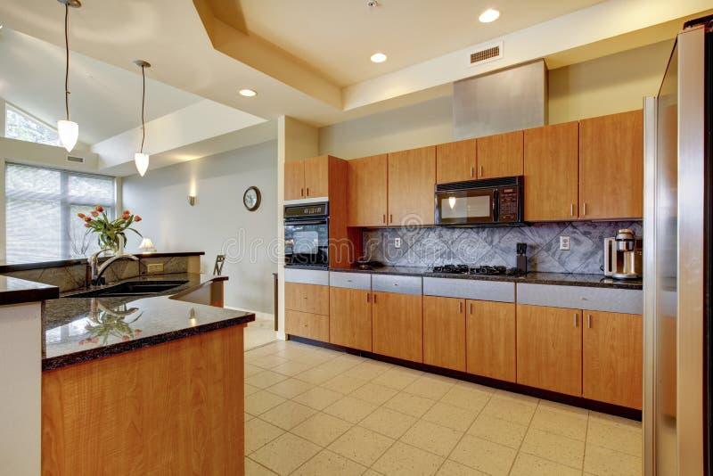 Grote moderne houten keuken met woonkamer en hoog plafond. royalty-vrije stock fotografie