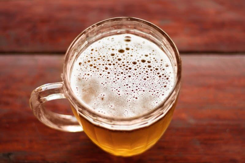 Grote mok van bier met schuim en bellen op een houten lijst stock fotografie