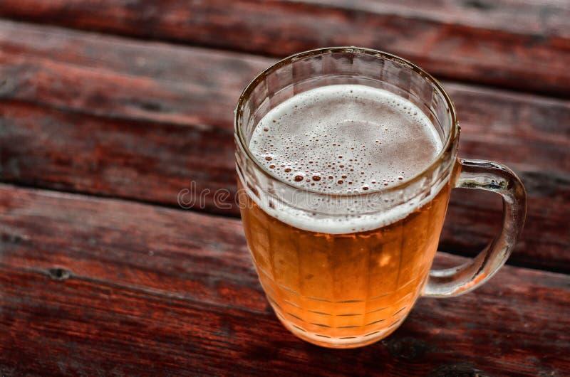 Grote mok van bier met schuim en bellen op een houten lijst royalty-vrije stock afbeeldingen