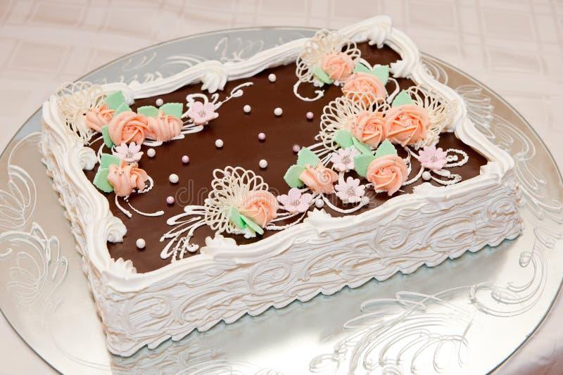 Grote mooie die chocoladecake met decoratieve bloemen en parel wordt verfraaid stock fotografie