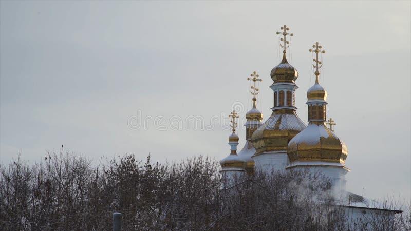 Grote, mooie kerk met sneeuw die op gouden koepels op duidelijke, grijze hemelachtergrond liggen voorraad De winterlandschap van stock foto's