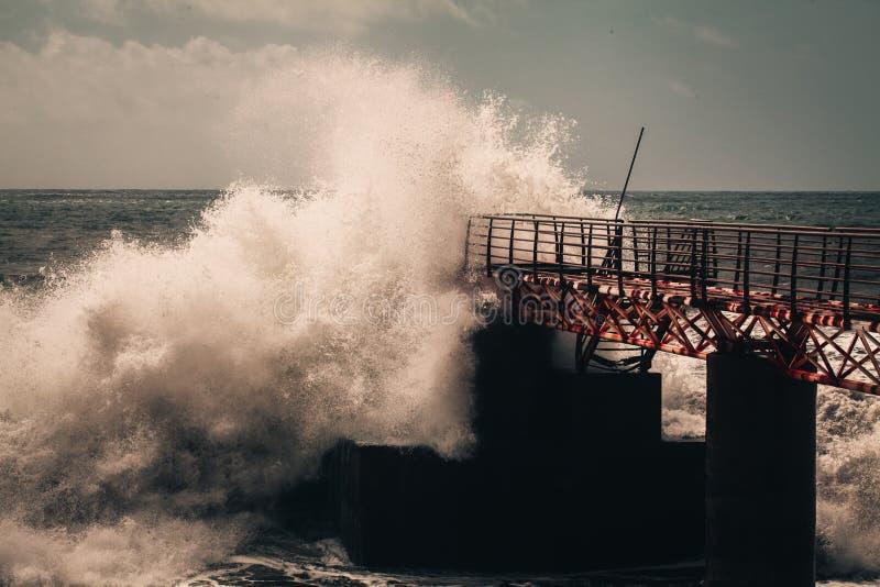 Grote oceaangolven die tegen de pijler breken stock fotografie