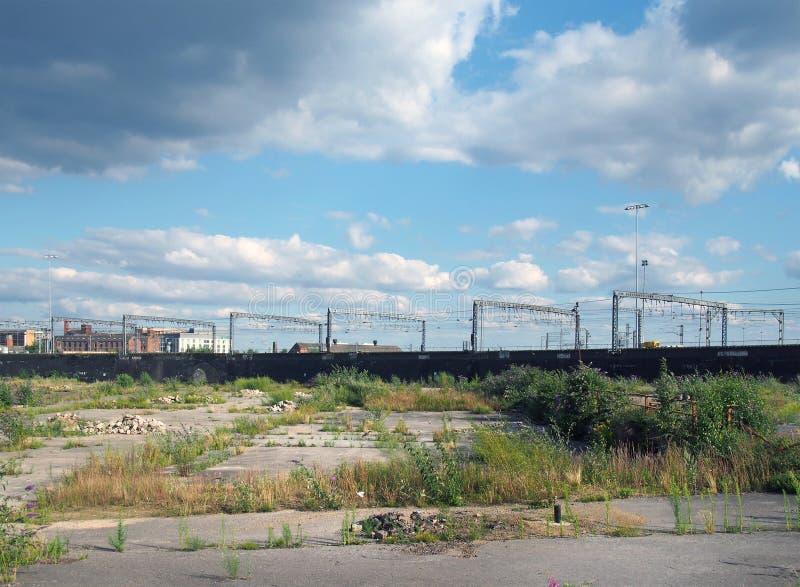 Grote ongebruikte stedelijke brownfieldplaats met open die land in gebarsten overwoekerd beton wordt behandeld die op ontwikkelin stock afbeelding