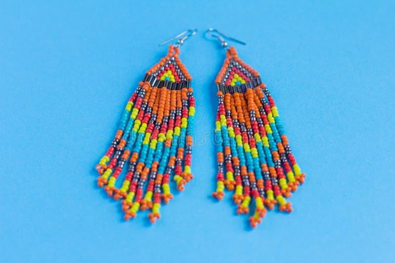 Grote oorringen die van multi-colored parels en bugelparels worden gemaakt, bohostijl, op een blauwe achtergrond stock afbeeldingen