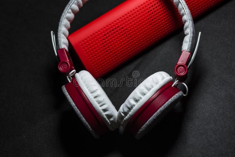 Grote oortelefoons van witte en rode kleuren Klein de draagbare sprekers Zwarte achtergrond Moderne mobiele elektronika gadgets royalty-vrije stock afbeeldingen