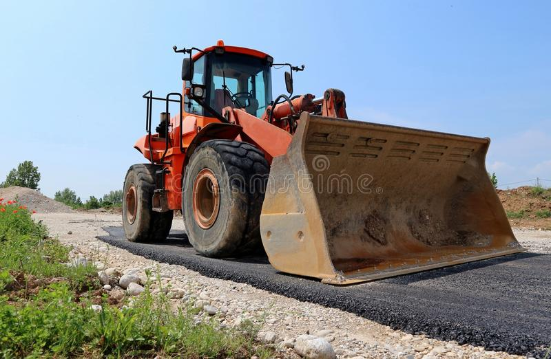 Grote oranje bulldozer op een half bedekte weg bij de bouwwerf stock foto's