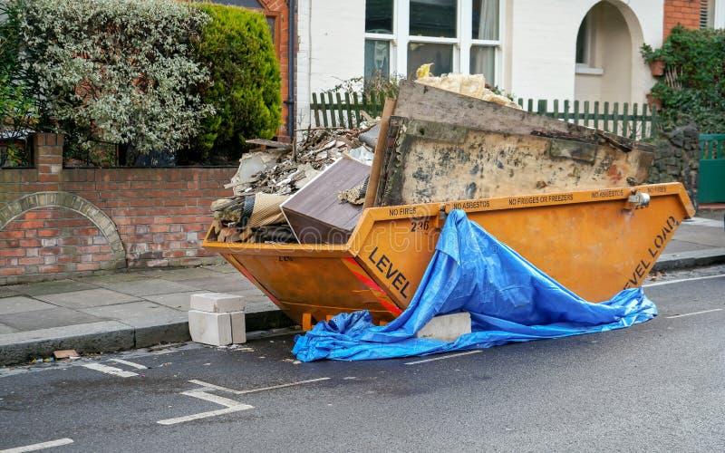 Grote oranje metaalskip container vooraan huis, volledig van vuilnis van huishoudenwederopbouw stock fotografie
