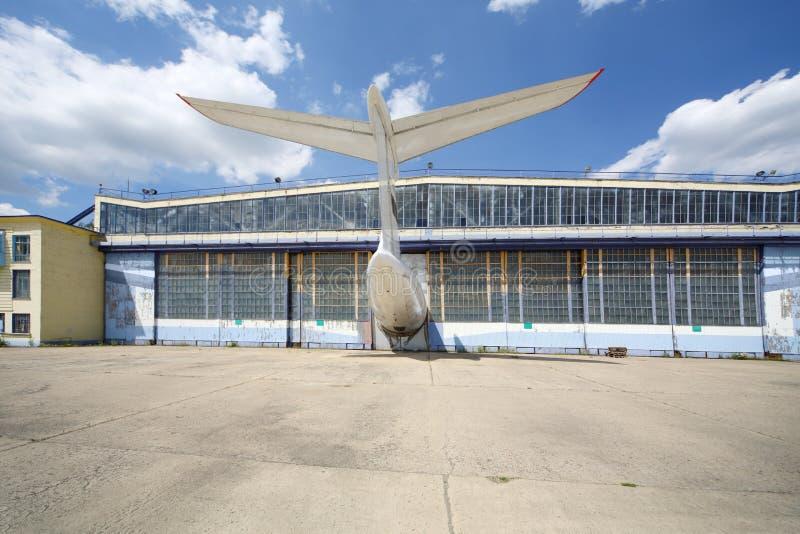 Grote oude geslagen vliegtuigenhanger met vooruitstekende staart van vliegtuig stock foto