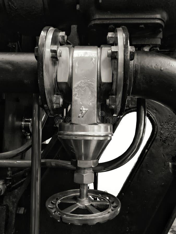 Grote oude metaal industriële klep met rond handvat opgezet op een grote zwarte machine met bouten en glanzende pijpen stock afbeelding