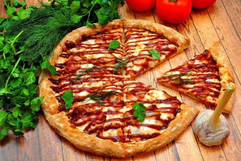 Grote Pizza met een barbecue op een houten lijst stock foto's