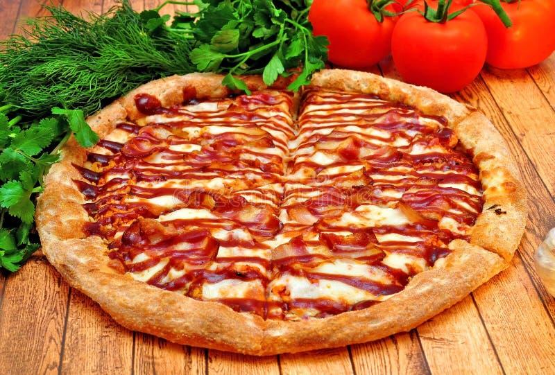 Grote Pizza met een barbecue op een houten lijst stock afbeeldingen