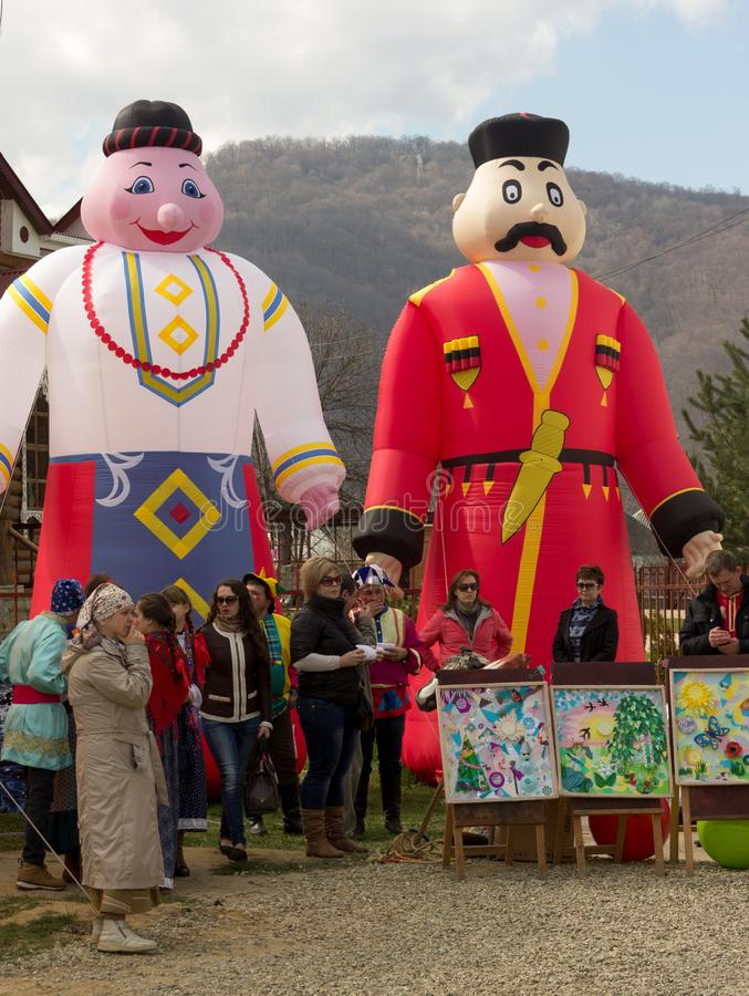 grote poppen opblaasbare cijfers die de mens en vrouw in traditionele kostuums en actoren en kunstenaars op de pannekoekdag afsch stock fotografie