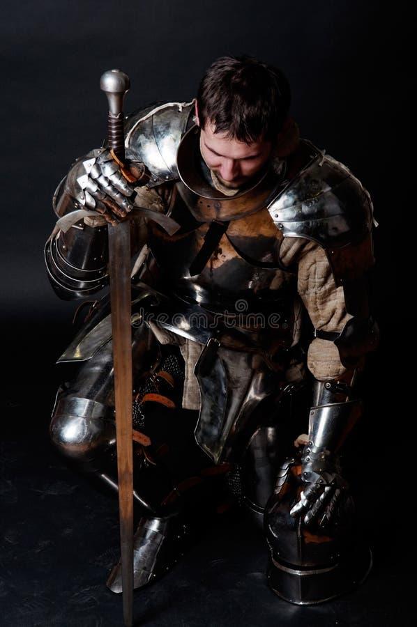 Grote ridder die zijn zwaard en helm houdt stock foto