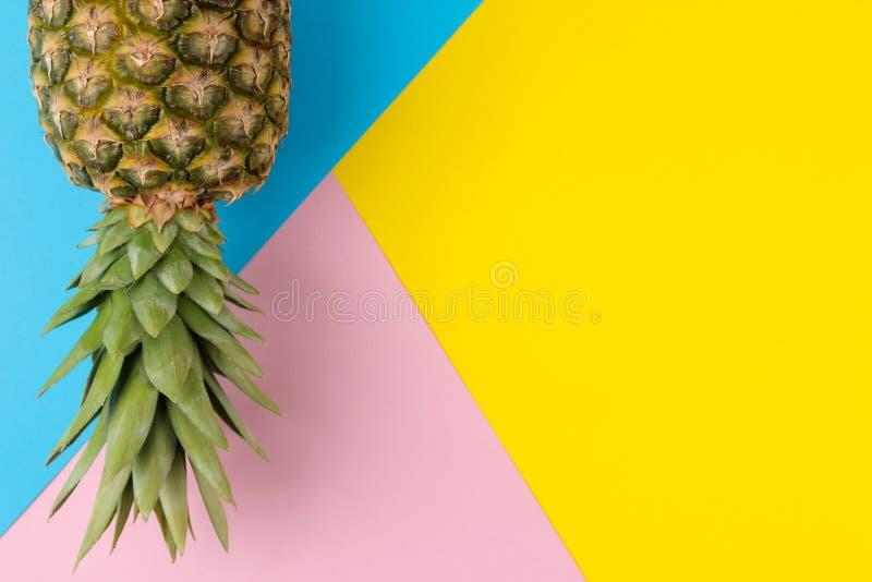Grote rijpe fruitananas op een heldere gele, blauwe en roze achtergrond De zomer Hoogste mening royalty-vrije stock afbeeldingen