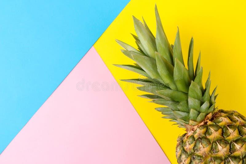 Grote rijpe fruitananas op een heldere gele, blauwe en roze achtergrond De zomer Hoogste mening stock foto