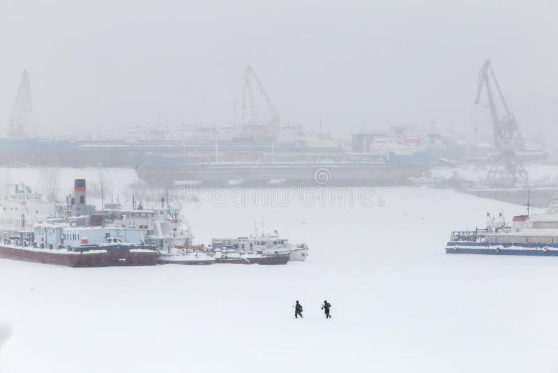 Grote rivierambachten op het de winterparkeren De schepen zijn bevroren in ijs Op een achtergrondhavenkranen royalty-vrije stock fotografie