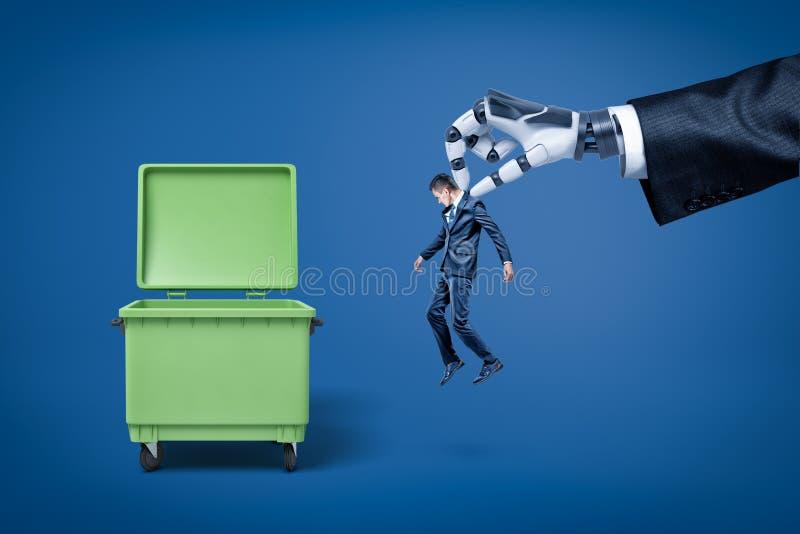 Grote robotachtig dient kostuum in houdend weinig zakenman om hem in vuilnisbak net te werpen stock foto