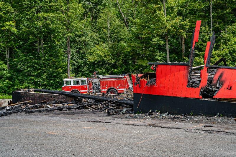Grote rode brandvrachtwagen dichtbij de uitgebrande winkel, gedoofde brand stock foto's
