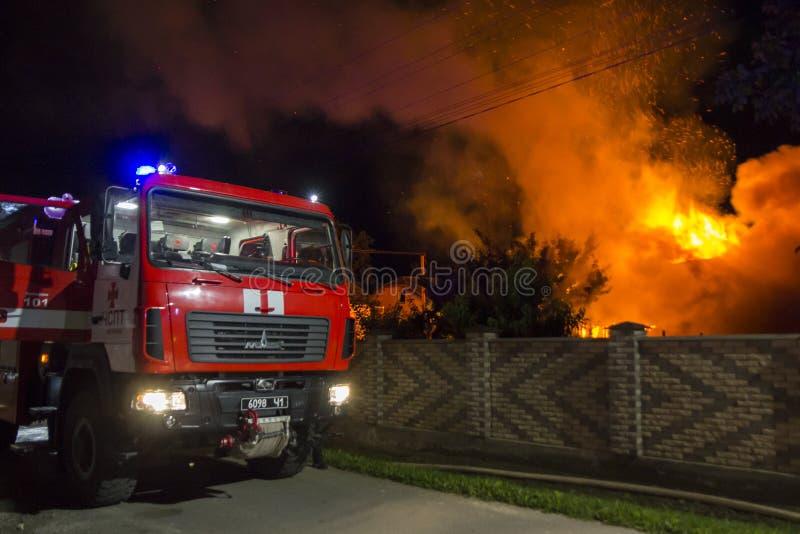 Grote rode die brandvrachtwagen bij baksteenomheining wordt geparkeerd bij het branden van houten schuur bij nacht Hoge oranje br royalty-vrije stock foto