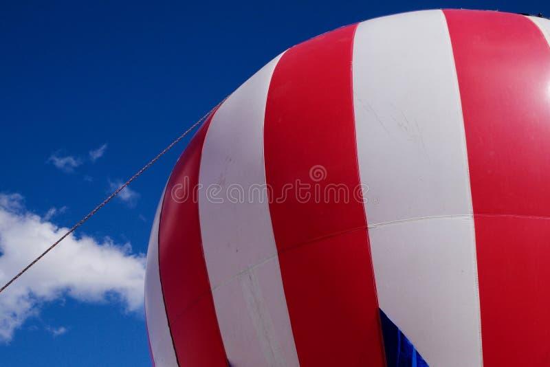 Grote rode en witte hete luchtballon tegen een blauwe hemel royalty-vrije stock afbeeldingen