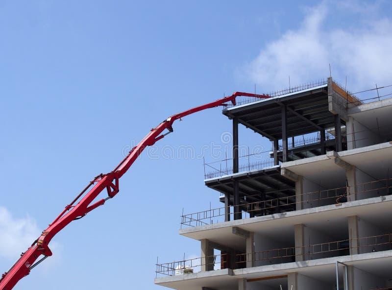 Grote rode gearticuleerde kraan die aan een grote moderne woonwijkplaats werken met concrete kader en veiligheidsbarrières stock foto's