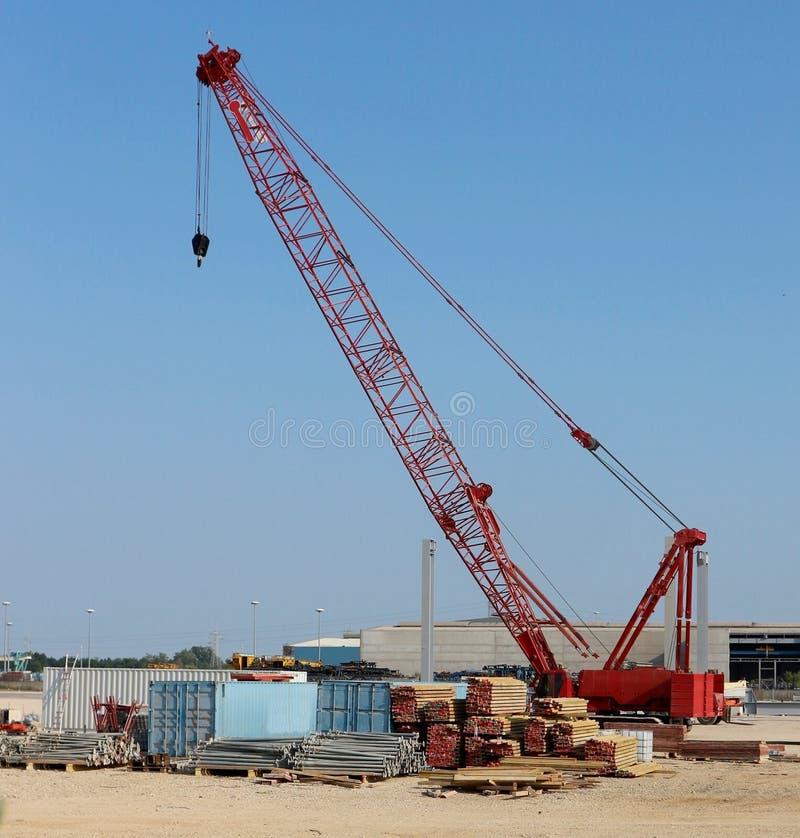 Grote rode telescopische kraan met bouwmaterialen op een industrieel bouwgebied royalty-vrije stock foto's