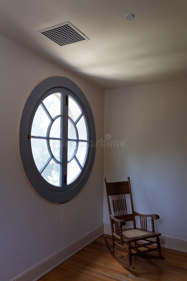 Grote ronde ronde ronde raam gezien vanuit de binnenkant, lege schommelstoel, metafoor voor veroudering, verlies, dood en verdrie stock foto