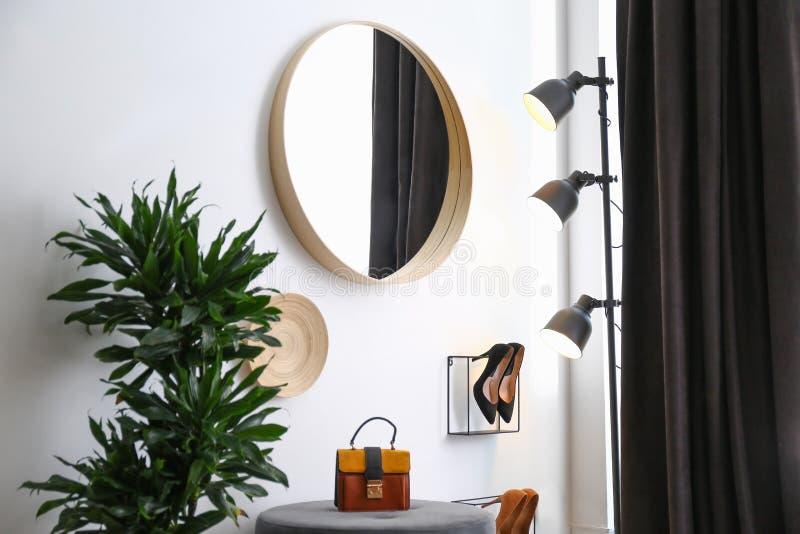 Grote ronde spiegel, houseplant en decor dichtbij witte muur in gang royalty-vrije stock fotografie