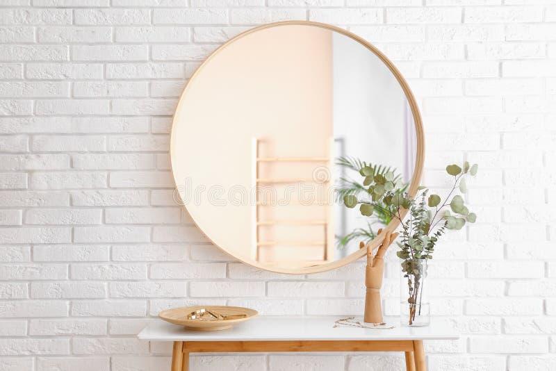 Grote ronde spiegel, lijst met juwelen en decor dichtbij bakstenen muur in gang stock afbeeldingen