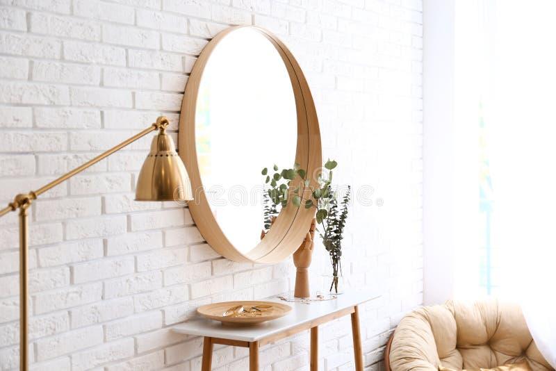 Grote ronde spiegel, lijst met juwelen en decor dichtbij bakstenen muur in gang stock fotografie