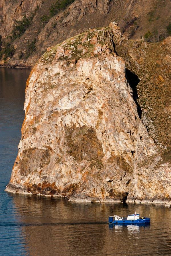Grote rots en klein schip De schipzeilen naast een grote rots stock afbeelding