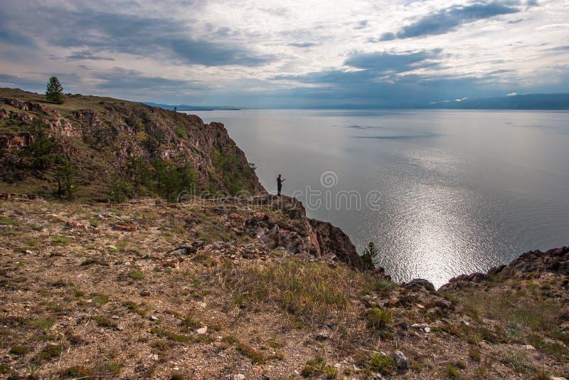 Grote rots met een mens op de rand Meer Baikal De hemel in de wolken royalty-vrije stock foto