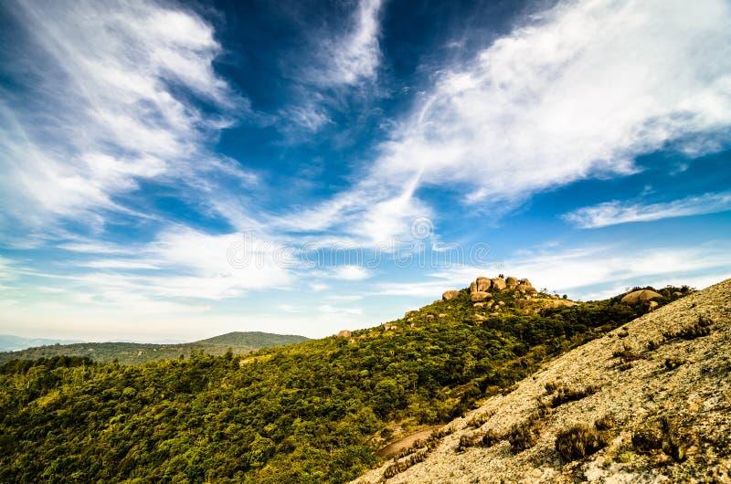Grote Rotsberg (Pedra Grande) in Atibaia, Sao Paulo, Brazilië met bos, diepe blauwe hemel en wolken stock foto's