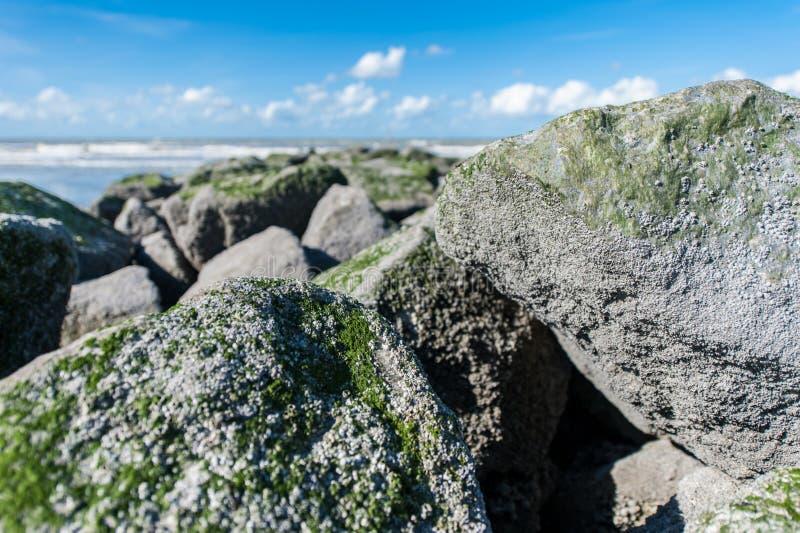 Grote rotsen op strand met blauwe hemel stock afbeeldingen