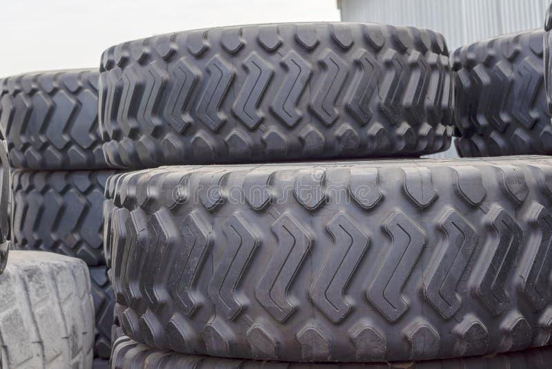 Grote rubberbanden voor vrachtwagens die op de straat liggen De zwarte banden sluiten omhoog met een groot loopvlak liggen op bov stock afbeelding