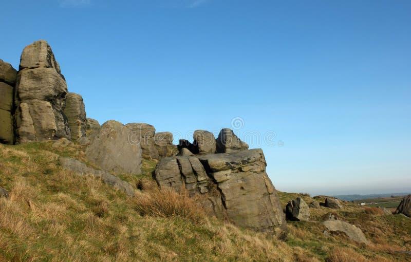 Grote ruwe gritstonedagzomende aardlaag bij bridestones een grote rotsvorming in de blauwe hemel van West-Yorkshire dichtbij todm royalty-vrije stock fotografie